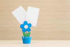 Closeup clamp photo in blue flower shape shape in flowerpot with black white paper on blurred wooden desk and wall background. Clamp photo in blue flower shape stock photos