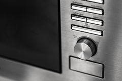 Closeup clean new kitchen microwave cooker knob heat volume switch. Elegant metal steel black and white royalty free stock photography