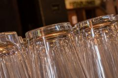 Closeup of shiny pint glasses in a row tipping from right to left. Closeup of clean and shiny pint glasses in a row tipping from right to left stock photos