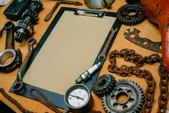 Closeup clipboard with paper for your info in the center of tools, gears on vintage metal background. Motorcycle equipment and. Closeup clipboard with paper for royalty free stock photos