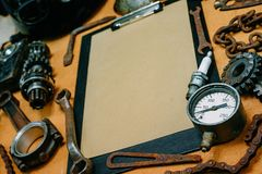 Closeup clipboard with paper for your info in the center of tools, gears on vintage metal background. Motorcycle equipment and. Closeup clipboard with paper for royalty free stock images