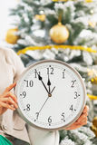 Closeup on clock in hand of woman in front of christmas tree Royalty Free Stock Images