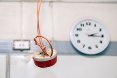 Closeup clock and installation and repair of electric cable, smoke detector, fire alarm system before installing. Concept testing royalty free stock images