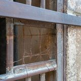 Closeup of a closed rusted iron bars of cell door in closed abandoned prison stock photo