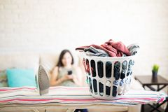 Closeup of clothes in basket next to iron. Laundry basket with iron on iron table and woman in blur background using smartphone Royalty Free Stock Photos