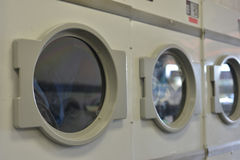 Washday Clothes Dryer. Closeup of clothes dryer at local laundromat Royalty Free Stock Photography