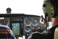 Closeup of a cockpit of cessna skyhawk 172 airplane with two pilots. stock photos