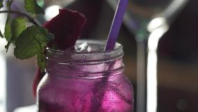 Dragon fruit cocktail at the bar. Closeup cocktail decorated with slice of dragon fruit at the bar - video in slow motion stock video footage