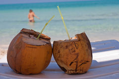 Closeup of Coconut Drinks. Closeup of two coconut drinks with straws on a beach chair with the Caribbean sea and a female swimmer in the background Stock Images