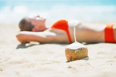 Closeup on coconut and young woman laying on beach in background Royalty Free Stock Photos
