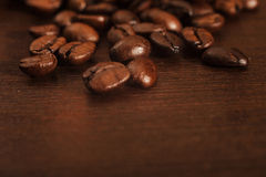 Closeup of coffee beans on a dark wooden surface. Closeup of coffee beans scattered on a dark textured wooden surface royalty free stock photos