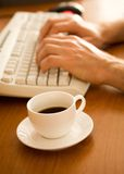 Closeup of coffee cup near keyboard Royalty Free Stock Photo