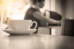 Closeup of coffee cup on table in coffee shop - tone black and white. Closeup of coffee cup on table in coffee shop - tone black and white Royalty Free Stock Images