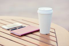 Closeup coffee cup, weekly organizer, smartphone, pen table city cafe Stock Photography
