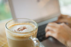 Closeup of coffee and  hand typing Stock Images