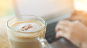 Closeup of coffee and  hand typing Royalty Free Stock Photography