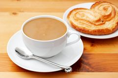 Closeup of coffee with milk. In white cup and a palmier pastry. Shot on light wood background Royalty Free Stock Photo