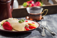 Closeup of coffee and pancakes with strawberries served on break Stock Image