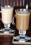 Closeup of coffee and tea. With milk in glass cups on cherry wood table Royalty Free Stock Photo