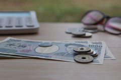 Closeup coin yen and banknotes Japanese and Calculator on wooden background. Currency of Japan. Stock Photos