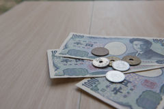 Closeup coin yen and banknotes Japanese  on wooden background. Currency of Japan. Stock Photo