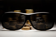 Closeup of coins behind pair of sunglasses Stock Photos