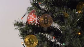 Coins of Bitcoin Payment System Hang on Christmas Tree Closeup