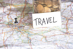 Closeup of coins in a jar with travel sign on a map. Royalty Free Stock Images