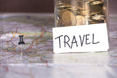 Closeup of coins in a jar with travel sign and a pin. Stock Image