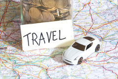 Closeup of coins in a jar with travel sign and a toy car on a ma Royalty Free Stock Photos
