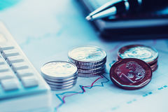 Closeup coins with line chart, pen and calculator Stock Photos