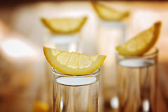 Closeup cold glass of vodka with lemon. Stock Photos