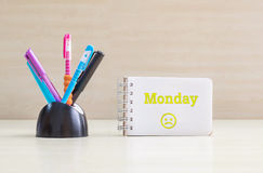 Closeup color pen with black ceramic desk tidy for pen and yellow monday word in white page and frown face emotion at the note boo Royalty Free Stock Photography