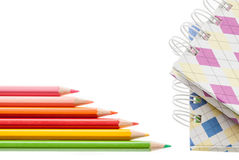Closeup color pencil and notebook on white background. Royalty Free Stock Image