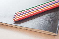Closeup color pencils on black notebook Stock Photos