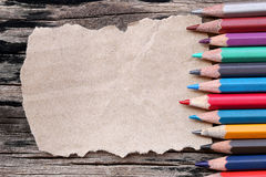 Closeup Color pencils concatenation on brown paper and old woode Royalty Free Stock Images