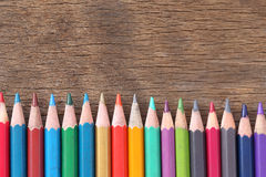 Closeup Color pencils concatenation on old wooden background. Royalty Free Stock Images