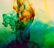 A closeup of colored dyes creating a unique pattern in water. royalty free stock photography
