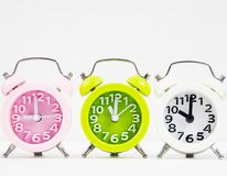 Closeup the colorful alarm clock stacked in row,green alarm clock put at the middle of pink and white colo. R,on white background stock photography
