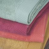 Colorful bath towels pile in store. Closeup of colorful bath towels pile in store Stock Photos