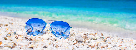 Closeup of colorful blue sunglasses on tropical beach Royalty Free Stock Image