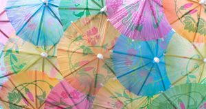 Colorful cocktail umbrellas full frame. Closeup colorful bright cocktail umbrellas in green, blue, yellow, orange, and pink; festive background; tropical royalty free stock images
