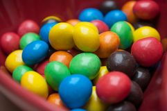 Colorful chocolate candies in a red bowl in shaped he royalty free stock photos