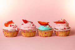 Closeup of colorful cupcakes with sprinkles and fresh strawberry Royalty Free Stock Images