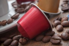 Colorful espresso coffee doses with coffee beans and. Closeup of colorful espresso coffee doses with coffee beans and cup of coffee on wooden table background royalty free stock photos