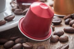 Colorful espresso coffee doses with coffee beans and. Closeup of colorful espresso coffee doses with coffee beans and cup of coffee on wooden table background stock image