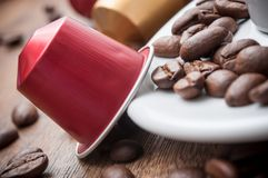 Colorful espresso coffee doses with coffee beans and. Closeup of colorful espresso coffee doses with coffee beans and cup of coffee on wooden table background royalty free stock photography
