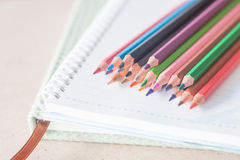 Closeup colorful pencil crayons on spiral notebook and green not Stock Image