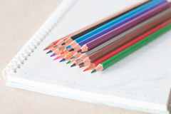 Closeup colorful pencil crayons on spiral notebook Stock Images
