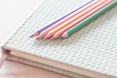 Closeup colorful pencils on green notebook Stock Image